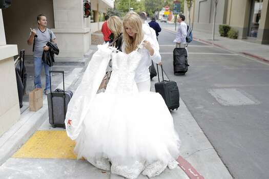 New bride Tori Campbell holds up her wedding dress after she and her new husband Colin Campbell were forced to evacuate from the Andaz Napa Hotel in Napa, Calif., after a strong earthquake hit the San Francisco Bay Area centered near American Canyon, on Sunday, August 24, 2014. Photo: Carlos Avila Gonzalez, The Chronicle
