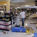 Kevin Coursey walks through the Lucky's store in Napa, Calif., as cleanup was underway after a strong earthquake hit the San Francisco Bay Area centered near American Canyon, on Sunday, August 24, 2014.
