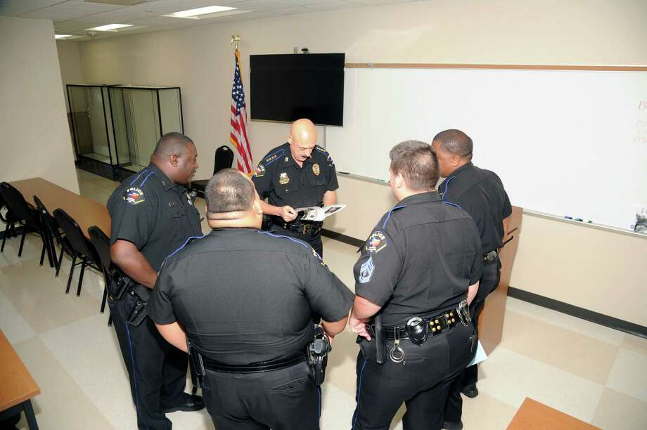 Cy-Fair school district police chief Alan Bragg, center, discusses some of the day's issues with some of the school district's police force. This year the chief says his department has 30 positions it is trying to fill. Photo: Eddy Matchette, Freelance / Freelance