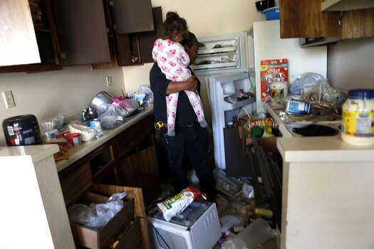 Raul Guzman holds his 3-year-old daughter, Mia, as he inspects the earthquake damage  in his apartment at Charter Oaks on Browns Valley Road in Napa. Photo: Scott Strazzante, The Chronicle