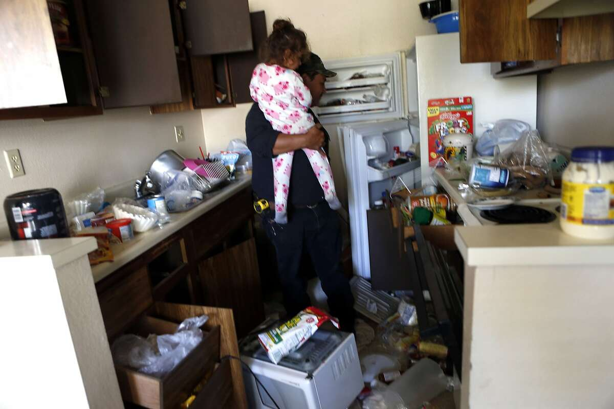 Raul Guzman holds his daughter Mia, 3, as he inspects the earthquake damage in his apartment at Charter Oaks on Browns Valley Road in Napa, Calif. on Sunday, August 24, 2014,