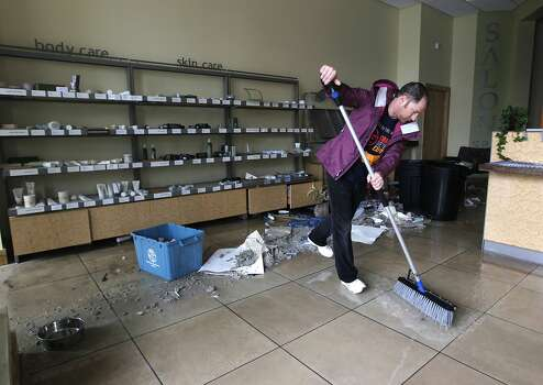 Andrew Healey sweeps water and debris from his wife's Sala Salon in Napa, Calif. on Sunday, Aug. 24, 2014, which suffered damage after a 6.0 earthquake jolted the Bay Area. Photo: Paul Chinn, The Chronicle