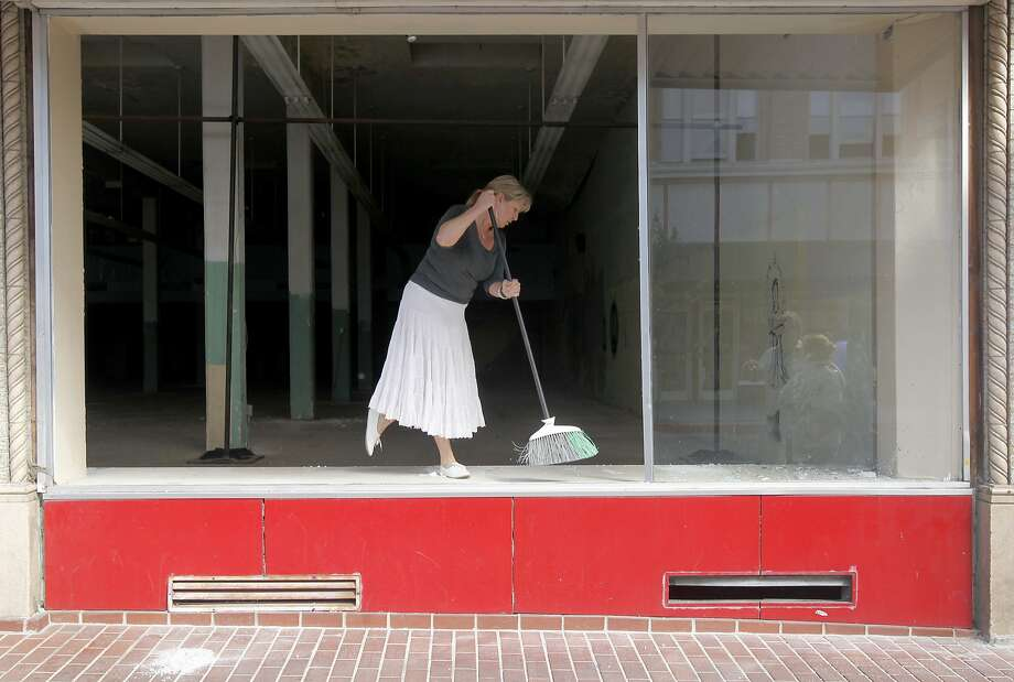 Kim Baker sweeps broken shards of glass from a vacant store in Napa, Calif. on Sunday, Aug. 24, 2014 after a 6.0 earthquake jolted the Bay Area. Photo: Paul Chinn, The Chronicle