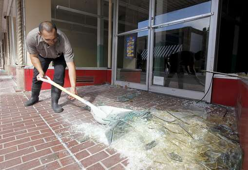 Juan Becerra shovels broken glass from the front of a vacant commerical property in Napa, Calif. on Sunday, Aug. 24, 2014 after a 6.0 earthquake jolted the Bay Area. Photo: Paul Chinn, The Chronicle