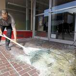 Juan Becerra shovels broken glass from the front of a vacant commerical property in Napa, Calif. on Sunday, Aug. 24, 2014 after a 6.0 earthquake jolted the Bay Area.