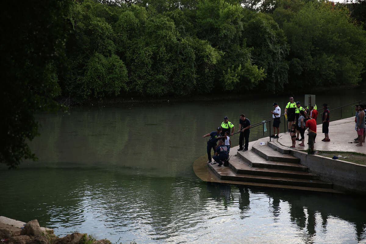 A boy points to a location of the Comal River to New Braunfels emergency personnel Saturday.