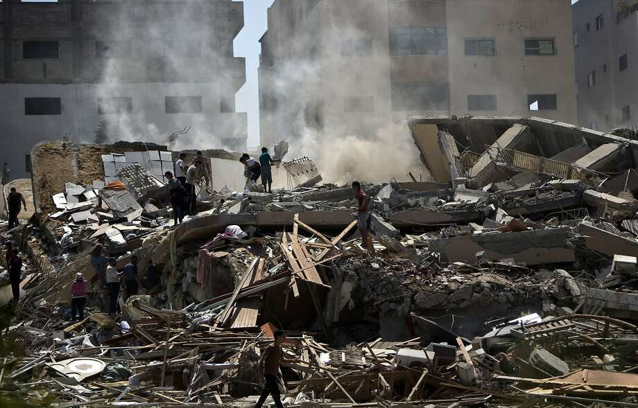 Palestinians search the rubble of a 12-story apartment after it was hit by an Israeli air strike Saturday. Photo: Mahmud Hams, AFP/Getty Images