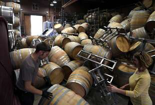 Saintsbury Winery's Ry Richards (left) and Chris Kajani work on removing the stacks of empty barrels that tumbled over after an earthquake in Napa, Calif. on Sunday, August 24, 2014,