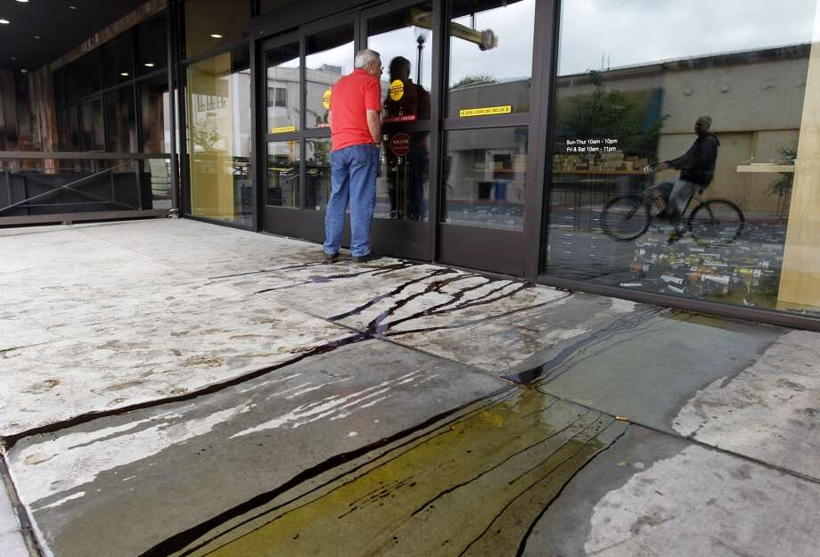 Olive oil and balsamic vinegar flows from the Lucero Olive Oil shop while bulding owner Michael Holcomb assesses the damage in Napa, Calif. on Sunday, Aug. 24, 2014 after a 6.0 earthquake jolted the Bay Area. Photo: The Chronicle