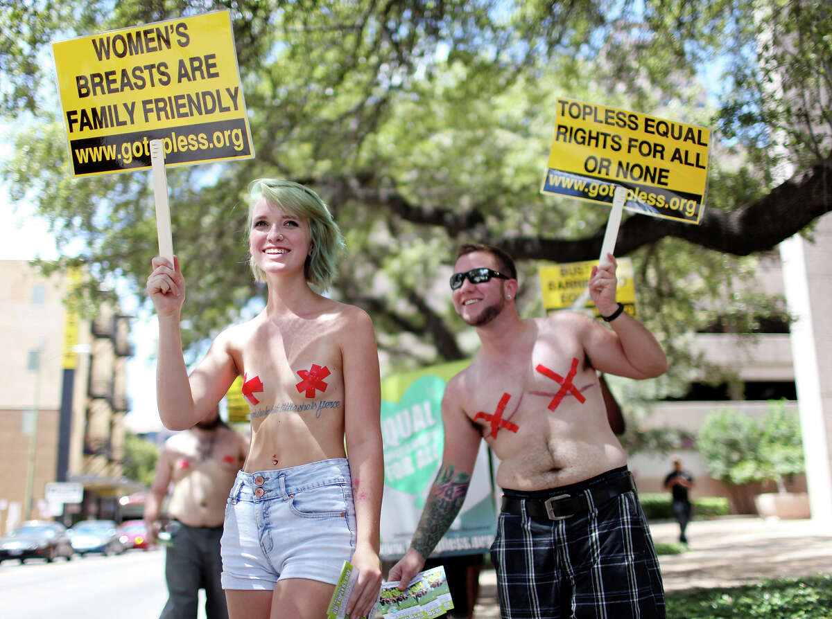 Hailey Jones, 19, (left) and Brian Nienhouse, 29, take part in a topless march around downtown Sunday Aug. 24, 2014. The march was part of the 7th annual Go Topless Day events held in over 60 cities worldwide. About 30 people took part in the event. For more information visit gotopless.org