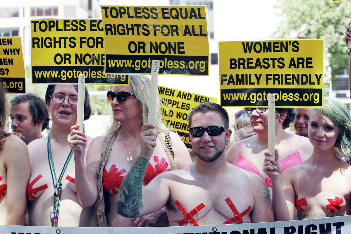 Participants in a topless march pose for photos Sunday Aug. 24, 2014 in Travis Park. The march was part of the 7th annual Go Topless Day events held in over 60 cities worldwide. About 30 people took part in the event. For more information visit gotopless.org