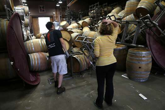 Saintsbury Winery's Kevin Kyle (left) and Chris Kajani work on removing the stacks of empty barrels that tumbled over after an earthquake in Napa, Calif. on Sunday, August 24, 2014, Photo: Scott Strazzante, The Chronicle