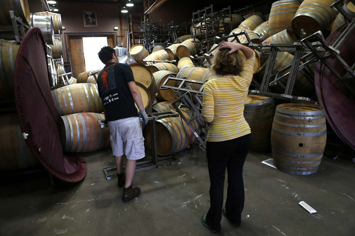 Saintsbury Winery's Kevin Kyle (left) and Chris Kajani work on removing the stacks of empty barrels that tumbled over after an earthquake in Napa, Calif. on Sunday, August 24, 2014,