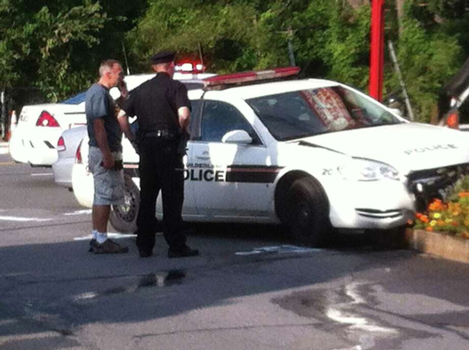 A Guilderland officer and another man with the damaged police car after the two-car collision on Western Avenue on Sunday afternoon, Aug. 24. Kenneth C. Crowe II / Times Union
