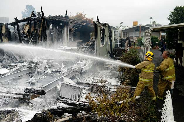 Napa County volunteer firefighters Mike Morisoli, left, and Steve Jones spray a mixture of water and foam on the remnants of a mobile home that caught fire and burned down after a magnitude 6.0 earthquake struck in the early morning of August 24, 2014,  in Napa, California. Photo: Alvin Jornada, Special To The Chronicle