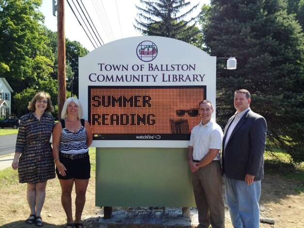 The town of Ballston Community Library officials stand beside single color digital sign, which has replaced two exterior signs, paid for in large part by a grant secured by state Sen. Hugh Farley. When the library surveyed the community in preparation, residents said the sign was the best way to let them know about programs and events. Because it is programmable it can be turned off at night to ensure it won?t disrupt neighbors.(Submitted photo)