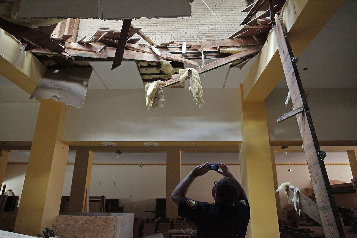 Dan Sarna of the Vallejo Fire Department takes a photo of a collapsed roof on Georgia St. on Sunday, August 24, 2014 in Vallejo, Calif. A 6.0 earthquake rattled much of the Bay Area early Sunday morning.