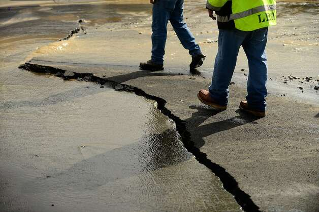 Napa Public Works employees inspect a buckled section of pavement that ruptured a water main in a residential neighborhood after a magnitude 6.0 earthquake struck in the early morning of August 24, 2014, in Napa, California. Photo: Alvin Jornada, Special To The Chronicle
