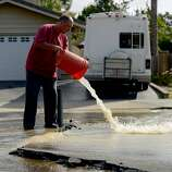 Edwin Wilkerson rinses out the bucket he is using to collect water from a broken water main, which cut off water service to his home, after a magnitude 6.0 earthquake struck in the early morning of August 24, 2014, in Napa, California.