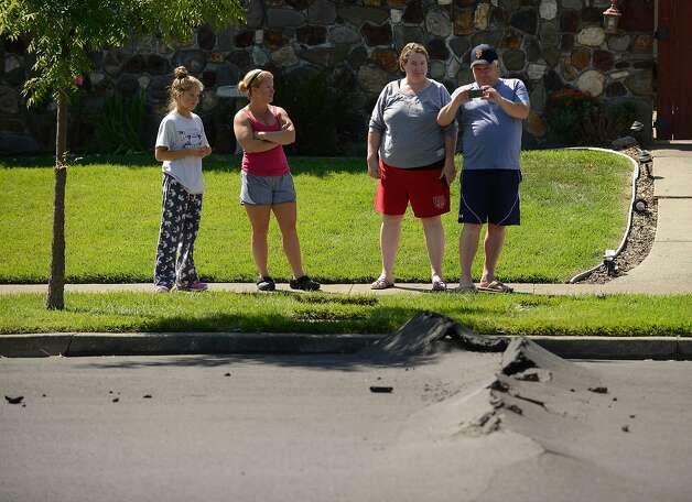 Makenna Harpe, left, age 13, and her mother Kelli talk with neighbors Kirsten and Toby Rompel as Toby snaps a photo of the buckled pavement on their street after a magnitude 6.0 earthquake struck in the early morning of August 24, 2014, in Napa, California. Photo: Alvin Jornada, Special To The Chronicle