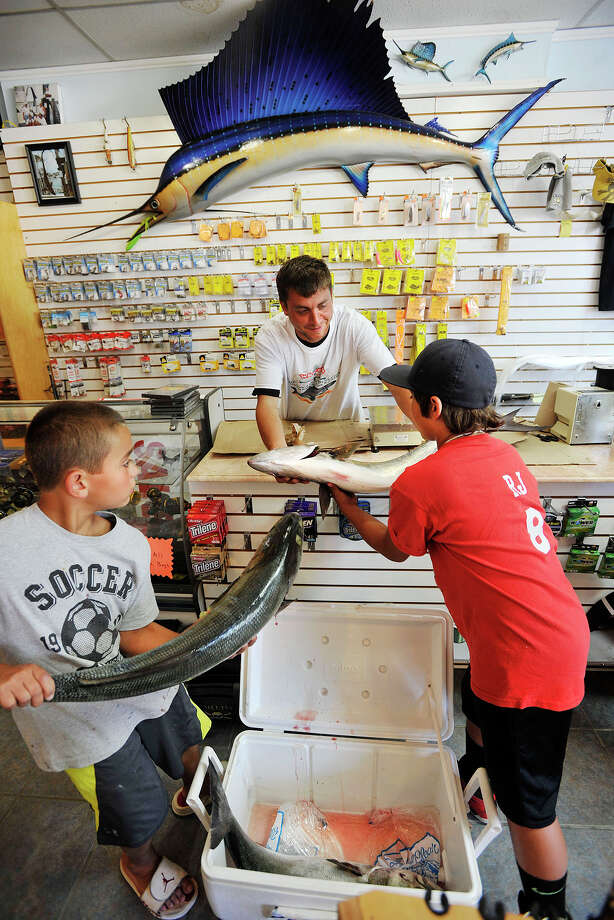 Manager Scott Denice helps brothers Justin, left, and R.J. Gierum, of Norwalk, weigh their fish at Fish Tales Bait & Tackle in Stamford, Conn., one of the official weigh stations, during the Port Jefferson Ferry WICC600 Greatest Bluefish Tournament on Earth on Sunday, Aug. 24, 2014. Photo: Jason Rearick / Stamford Advocate