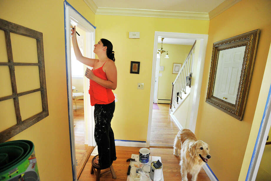 Megan Ricklic paints a doorway as the family dog, Riesling, looks on at the Ricklic home in Stamford, Conn., on Sunday, Aug. 24, 2014. Photo: Jason Rearick / Stamford Advocate