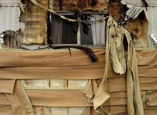 Melted siding sags off a mobile home which was next door to a mobile home that burned to the ground in the Napa Valley Mobile Home Park after a magnitude 6.0 earthquake struck in the early morning of August 24, 2014, in Napa, California. after a magnitude 6.0 earthquake struck in the early morning of August 24, 2014, in Napa, California. Photo: Alvin Jornada, Special To The Chronicle