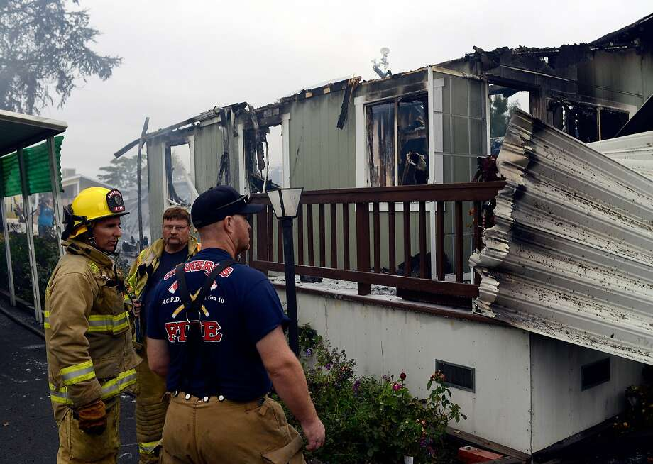 Firefighters monitor smoldering debris at a Napa mobile home park Sunday. Photo: Alvin Jornada, Special To The Chronicle