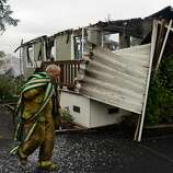 Firefighter Brett Skillings carries a firehose back to the fire engine while mopping up a section of Napa Valley Mobile Home Park where four homes burned to the ground after a magnitude 6.0 earthquake struck in the early morning of August 24, 2014, in Napa, California.