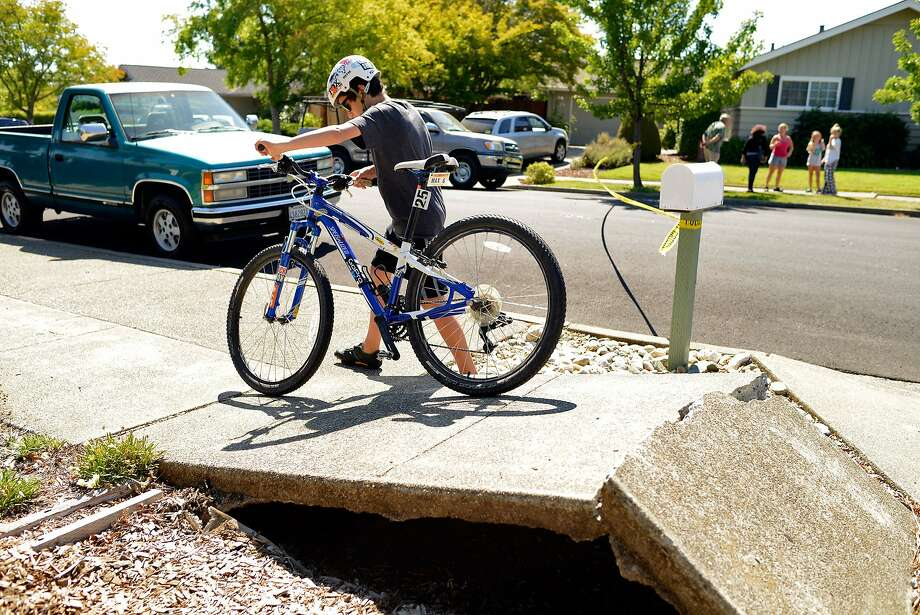 Max Gilseman, age 11, walks his bike over a buckled section of sidewalk in his Napa neighborhood after a magnitude 6.0 earthquake struck in the early morning of August 24, 2014, in Napa, California. Photo: Alvin Jornada, Special To The Chronicle