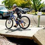 Max Gilseman, age 11, walks his bike over a buckled section of sidewalk in his Napa neighborhood after a magnitude 6.0 earthquake struck in the early morning of August 24, 2014, in Napa, California.