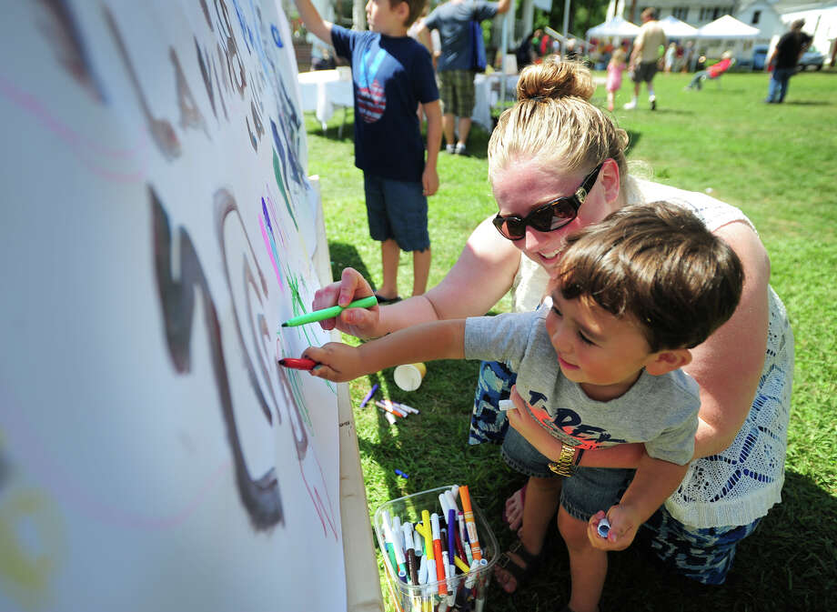 Erika Sievert draws with her nephew Nicholas Orgel, 2, both of Stratford, at the Artists & Artisans in Paradise fair on Paradise Green in Stratford, Conn. on Sunday, August 24, 2014. Photo: Brian A. Pounds / Connecticut Post