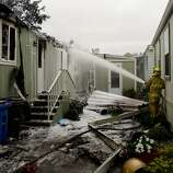 Napa County volunteer firefighter Mike Morisoli sprays a mixture of water and foam on a persistent hot spot on a mobile home that caught fire inside Napa Valley Mobile Home Park after a magnitude 6.0 earthquake struck in the early morning of August 24, 2014, in Napa, California.