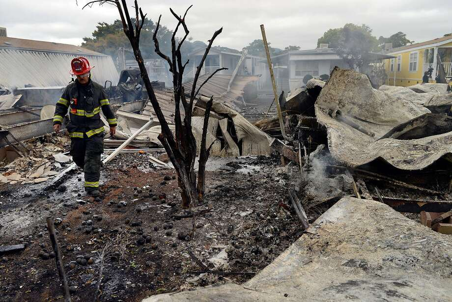 City of Napa Fire Captain Steve Becker walks through smoldering rubble of a group of mobile homes that burned to the ground in the Napa Valley Mobile Home Park after a magnitude 6.0 earthquake struck in the early morning of August 24, 2014, in Napa, California. Photo: Alvin Jornada, Special To The Chronicle
