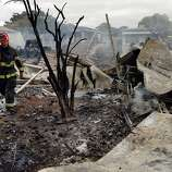 City of Napa Fire Captain Steve Becker walks through smoldering rubble of a group of mobile homes that burned to the ground in the Napa Valley Mobile Home Park after a magnitude 6.0 earthquake struck in the early morning of August 24, 2014, in Napa, California.