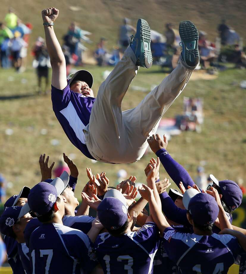 South Korea players celebrate by tossing manager Jong Wook Park into the air. Photo: Matt Slocum, Associated Press