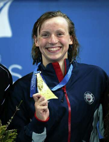 Katie Ledecky of the U.S. smiles as she poses with her gold medal after she set a new world record in her women's 1500m freestyle final at the Pan Pacific swimming championships in Gold Coast, Australia, Sunday, Aug. 24, 2014. Ledecky won the race setting a new world record of 15 minutes, 28.36 seconds.(AP Photo/Rick Rycroft) ORG XMIT: XGC148 Photo: Rick Rycroft / AP