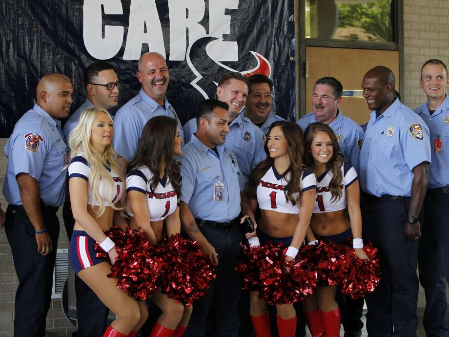 Houston Fire Department Captain Brad Hawthorne, back row, laughs as he and other members of HFD's Station 18 get their photos taken with Texans cheerleaders at Station 18 on Sunday. Hawthorne and Wyble were being honored by the Texans, for their actions in March, when the two rescued a worker, Curtis Reissig, from a Montrose apartment building, which caught on fire while under construction. Photo: Karen Warren, Houston Chronicle