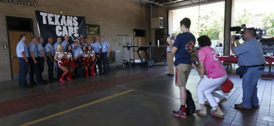 Members of the Houston Fire Department's Station 18 get their photos taken with Texan cheerleaders at Station 18 Photo: Karen Warren, Houston Chronicle
