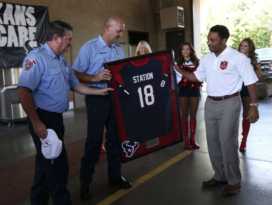 "Texans ambassador J.J. Moses hands Senior Captain Brad Hawthorne and Engineer Operator Dwayne Wyble a Texans jersey with an ""18"" on it at Station 18, Sunday, Aug. 24, 2014, in Houston. Hawthorne and Wyble were being honored by the Texans, for their actions in March, when the two rescued a worker, Curtis Reissig, from a Montrose apartment building, which caught on fire while under construction. Photo: Karen Warren, Houston Chronicle"