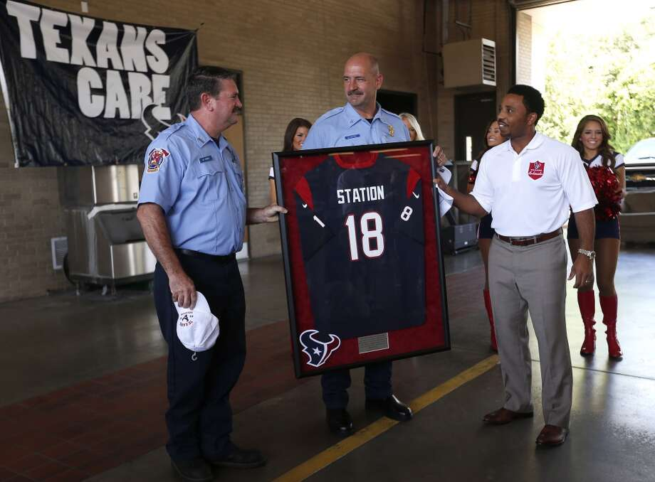 "Texans ambassador J.J. Moses hands Senior Captain Brad Hawthorne and Engineer Operator Dwayne Wyble a Texans jersey with an ""18"" on it at Station 18, Photo: Karen Warren, Houston Chronicle"