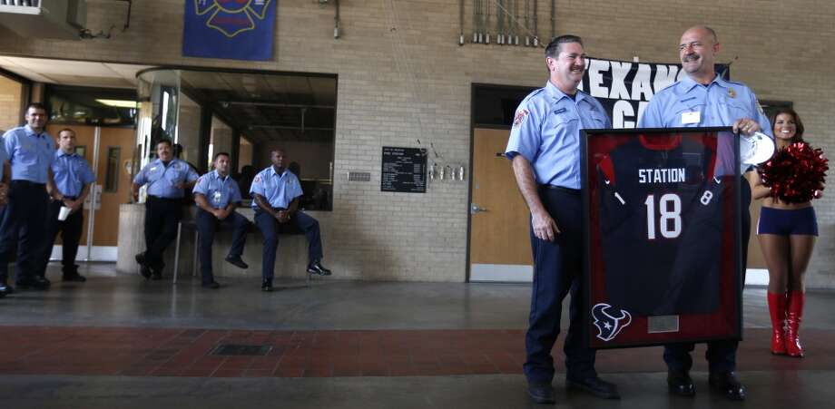 "Houston Fire Department Engineer Operator Dwayne Wyble, left, and Senior Captain Brad Hawthorne,right, hold a Texans jersey with an ""18"" on it at Station 18, Photo: Karen Warren, Houston Chronicle"