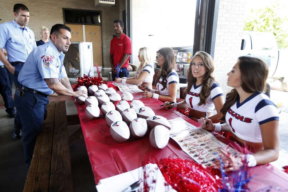 Texans cheerleaders sign autographs for firefighters at Station 18. Photo: Karen Warren, Houston Chronicle