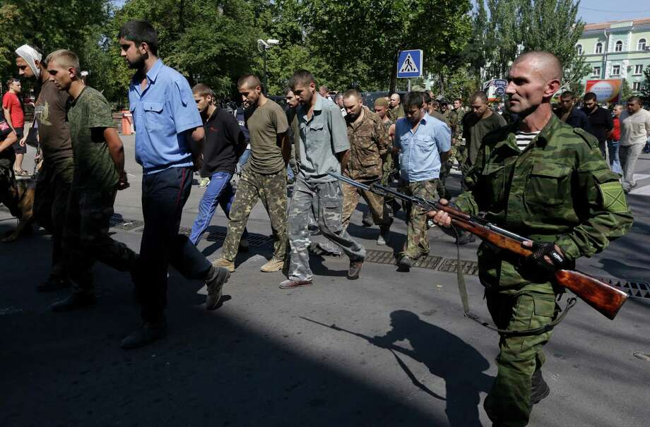 Pro-Russian rebels escorting captured Ukrainian army prisoners on central square in Donetsk, eastern Ukraine, Sunday, Aug. 24, 2014. Ukraine has retaken control of much of its eastern territory bordering Russia in the last few weeks, but fierce fighting for the rebel-held cities of Donetsk and Luhansk persists. (AP Photo/Sergei Grits) Photo: Sergei Grits, STF / AP