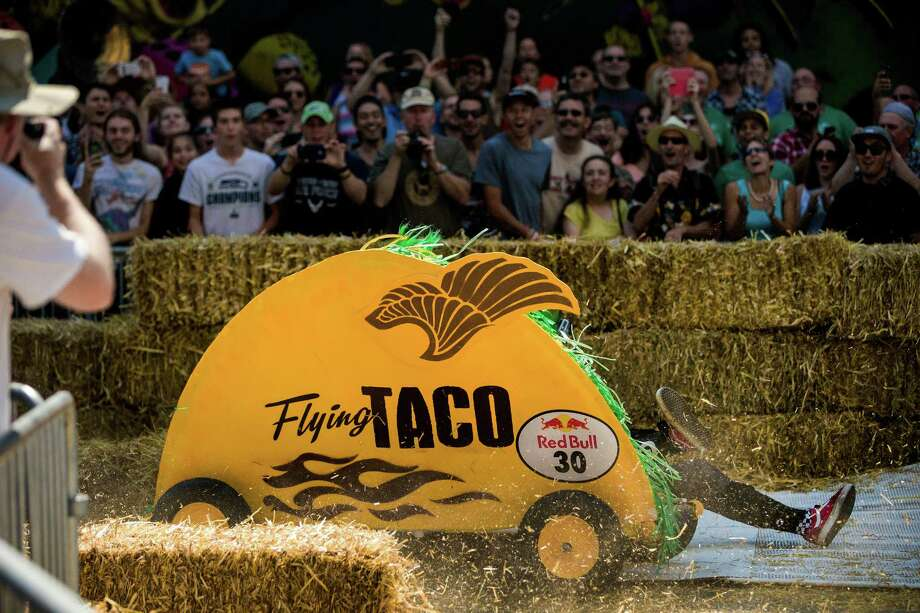 With sneakered feet flying, team Flying Taco crashes while rounding the curved turn near the finish line at the bottom of Yesler Way during the Red Bull Soapbox Race Sunday, August 24, 2014, in downtown Seattle, Washington. The rickety vehicles reached speeds of 40 miles per hour, sometimes plowing into the straw walls of the raceway. The first Red Bull Soapbox Race took place in Belgium in 2000, and has since visited almost 30 countries. Photo: JORDAN STEAD, SEATTLEPI.COM / SEATTLEPI.COM