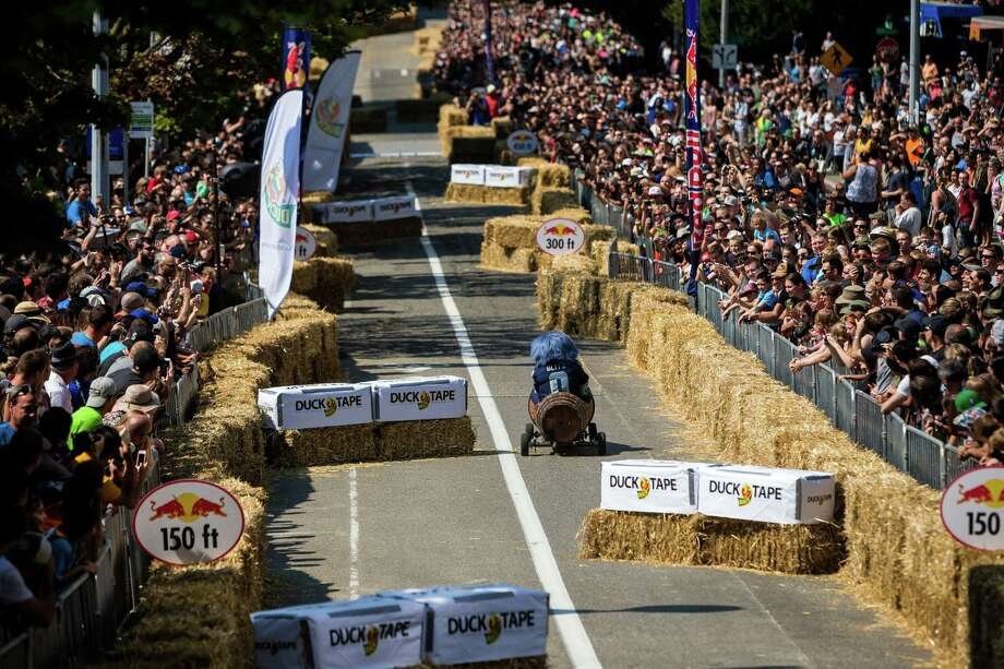 Seahawks mascot Blitz bombs down the steep grade of Yesler Way - with jumps and hard turns included - at the Red Bull Soapbox Race Sunday, August 24, 2014, in downtown Seattle, Washington. The rickety vehicles reached speeds of 40 miles per hour, sometimes plowing into the straw walls of the raceway. The first Red Bull Soapbox Race took place in Belgium in 2000, and has since visited almost 30 countries. Photo: JORDAN STEAD, SEATTLEPI.COM / SEATTLEPI.COM