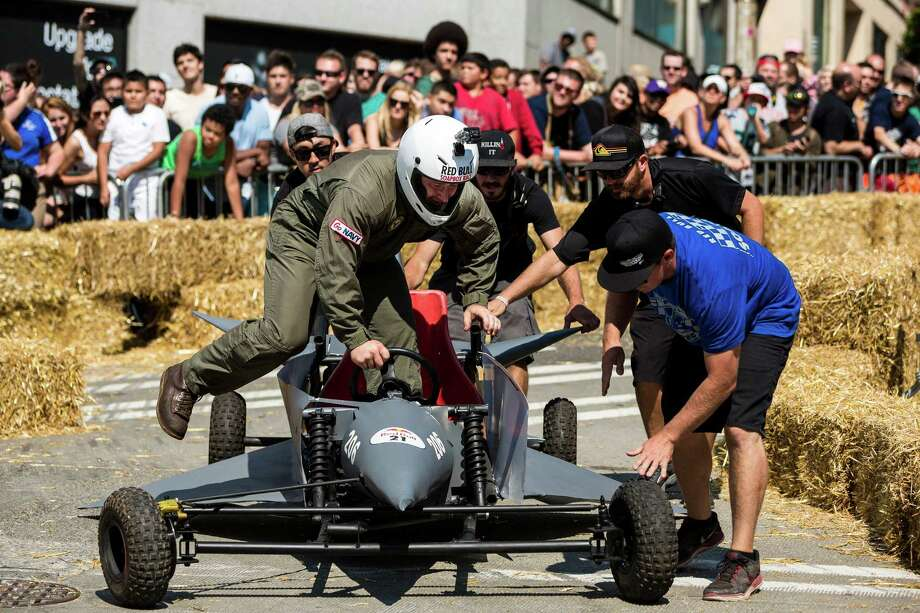 A driver is helped back into his vehicle after crashing near the finish line at the bottom of Yesler Way during the Red Bull Soapbox Race Sunday, August 24, 2014, in downtown Seattle, Washington. The rickety vehicles reached speeds of 40 miles per hour, sometimes plowing into the straw walls of the raceway. The first Red Bull Soapbox Race took place in Belgium in 2000, and has since visited almost 30 countries. Photo: JORDAN STEAD, SEATTLEPI.COM / SEATTLEPI.COM