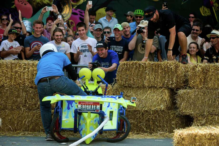 Crowds laugh and photograph an unlucky driver who crashed near the finish line at the bottom of Yesler Way during the Red Bull Soapbox Race Sunday, August 24, 2014, in downtown Seattle, Washington. The rickety vehicles reached speeds of 40 miles per hour, sometimes plowing into the straw walls of the raceway. The first Red Bull Soapbox Race took place in Belgium in 2000, and has since visited almost 30 countries. Photo: JORDAN STEAD, SEATTLEPI.COM / SEATTLEPI.COM