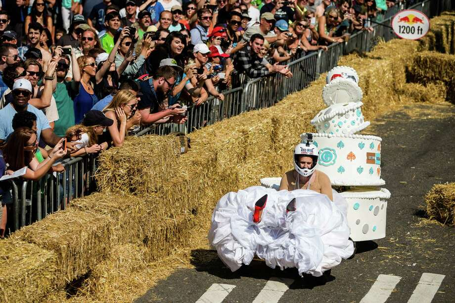 Teams round the curved turn near the finish line at the bottom of Yesler Way during the Red Bull Soapbox Race Sunday, August 24, 2014, in downtown Seattle, Washington. The rickety vehicles reached speeds of 40 miles per hour, sometimes plowing into the straw walls of the raceway. The first Red Bull Soapbox Race took place in Belgium in 2000, and has since visited almost 30 countries. Photo: JORDAN STEAD, SEATTLEPI.COM / SEATTLEPI.COM