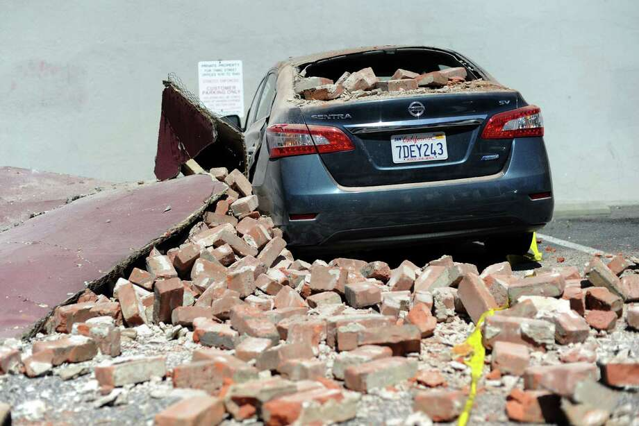 A car damaged by falling bricks is seen in downtown Napa, California after earthquake struck the area in the early hours of August 24, 2014. California's governor Jerry Brown declared a state of emergency Sunday following a strong 6.0-magnitude earthquake that seriously injured three people including a child and ignited fires in the scenic Napa valley wine region. The US Geological Service said that the quake was the most powerful to hit the San Francisco Bay area since the 1989 6.9-magnitude Loma Prieta earthquake. AFP PHOTO/JOSH EDELSONJosh Edelson/AFP/Getty Images ORG XMIT: 508890925 Photo: JOSH EDELSON / AFP